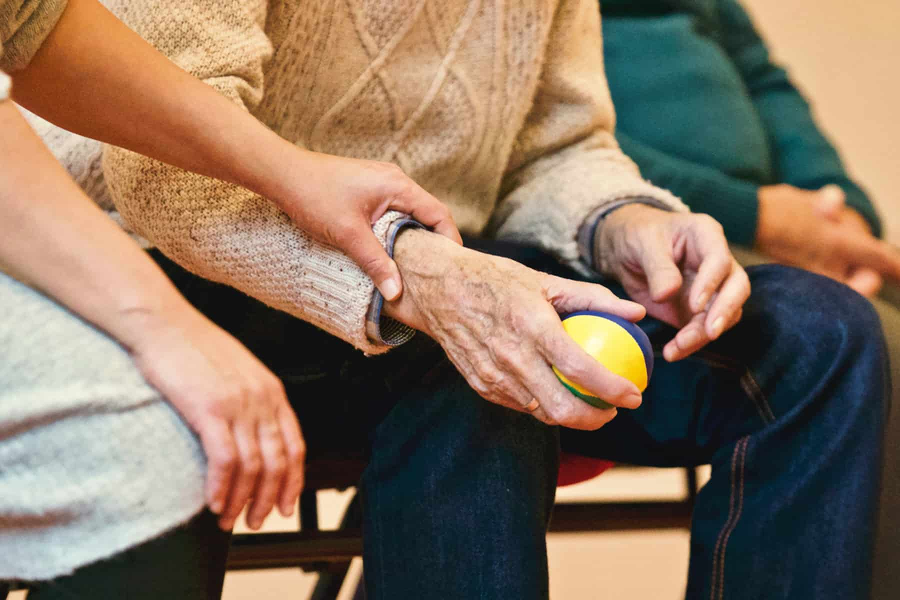old man holding ball as part of pain treatment