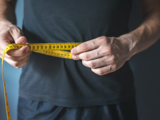 man holding measuring tape around his waist