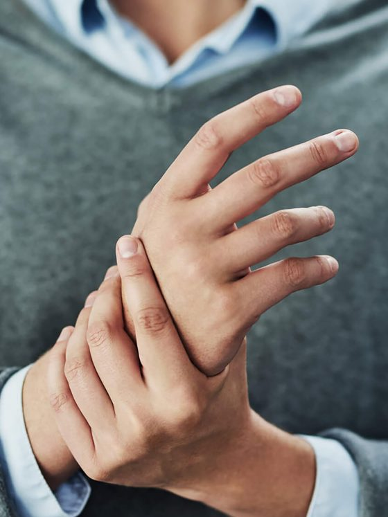 person with arthritis holding hand in pain