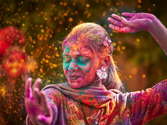 Young Indian woman with paint covered face Dancing during Holi