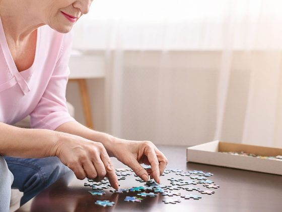 Elderly woman playing jigsaw puzzle on wooden table at home
