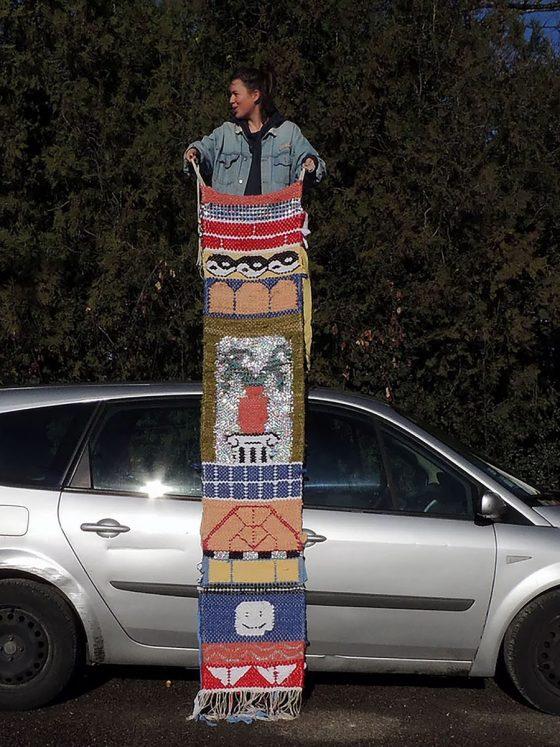 Delphine Dénéréaz standing on topof a car with her artwork