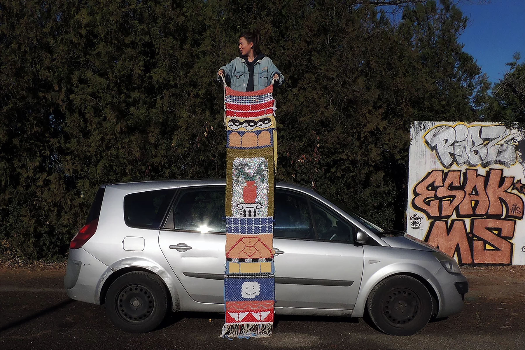 Delphine Dénéréaz standing on topof a car with her artwork