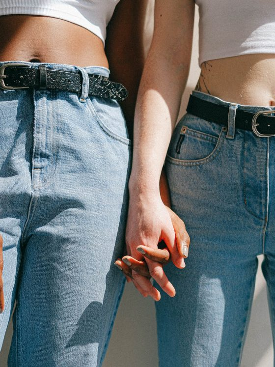 two women in jeans holding hands