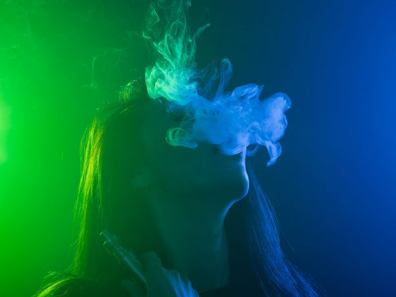 young woman in neon blue and green smoke with vape