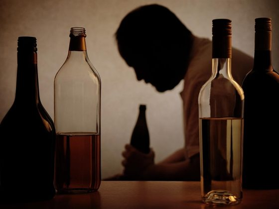 silhouette of a person drinking behind bottles of alcohol