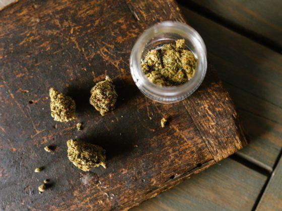 cannabis flower in a jar on a wooden board